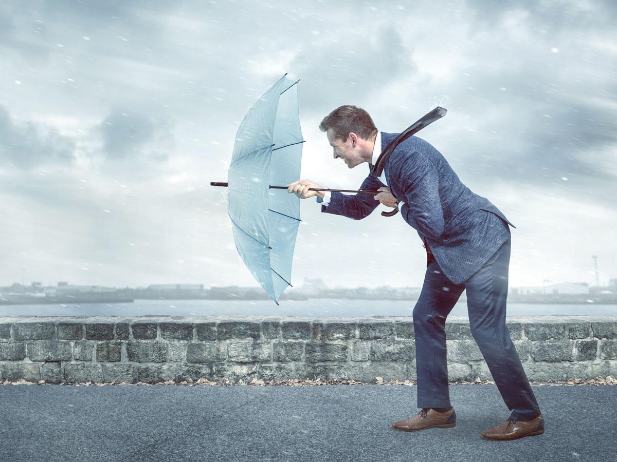 Mann stemmt sich mit Regenschirm gegen Sturm als Symbol für das Lernen von Resilienz